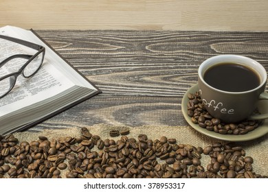 A cup of coffee with scattered coffee beans and open book with eyeglasses are  stands on a piece of burlap.