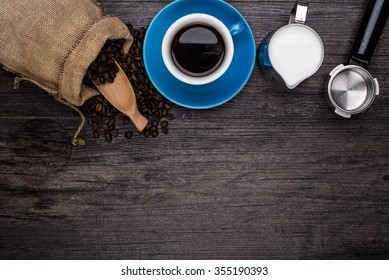 cup of coffee with scattered coffee grains are on the wood background