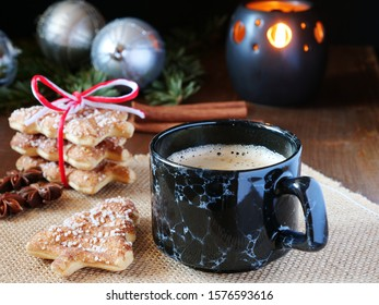 Cup of coffee served with Christmas tree shaped cinnamon biscuits in a rustic setup, dark background.