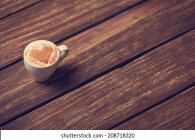 Cup of coffee with shape heart on wooden table.