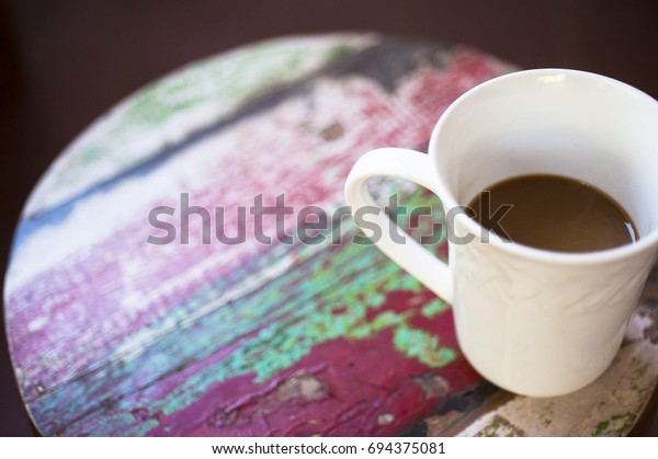 A cup of coffee sitting on a colorful wood stool in Maui, Hawaii.