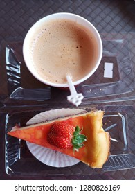 a cup of coffee and a slice of strawberry cake for hi-tea dessert