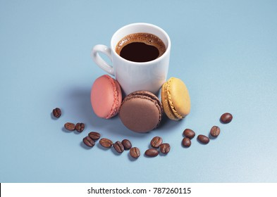Cup of coffee with small colorful macaroons on blue background