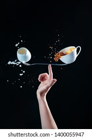 Cup of coffee and a small jug of milk balancing on a long spoon on the tip of a finger. Barista making a balanced latte. Creative coffee concept on a black background.