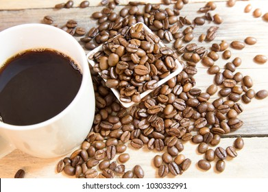 A cup of coffee with small white ceramic dish full of coffee beans on wooden bakcground.