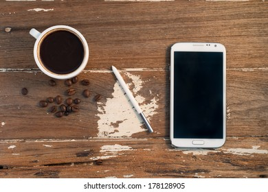 cup and coffee and smart phone  on wood texture.