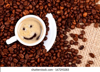 Cup of coffee with smiley face on coffee beans and burlap background