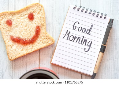 Cup Of Coffee And Smiling Face Toast Of Jam With Notes Good Morning On Table From Above.