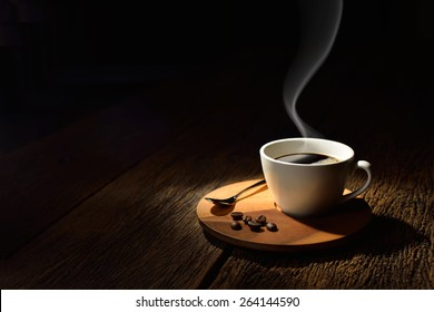 Cup of coffee with smoke and coffee beans on old wooden background, This photo is available without smoke