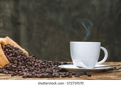 Cup of coffee with smoke and coffee beans on old wooden background.