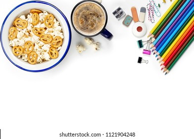 Cup of coffee with snacks and school stationery materials such as crayons, markers, clips, puncher, magnifying glass, erasers on white office table desk. Top view, flat lay with copy space