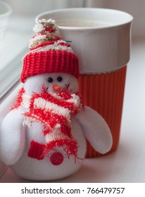 Cup of coffee and snowman toy. Winter season. Christmas comes soon. Red bright colours.