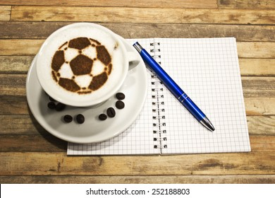 A cup of coffee with soccer ball , pencil, paper,