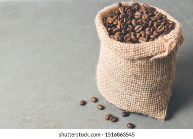 Cup of coffee with some cookies and coffee beans in jute sack.