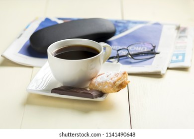 a cup of coffee and something sweet to the morning newspaper - nice start to the day