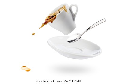 cup of coffee spills with saucer and spoon and coffee falls on white background