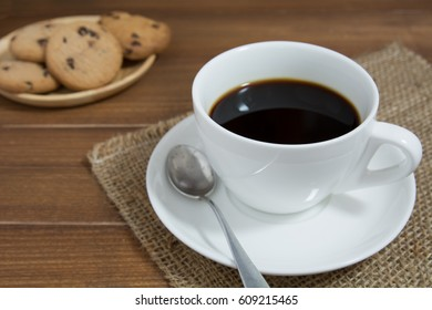 cup of coffee, spoon and chocolate chip cookies on wooden background.