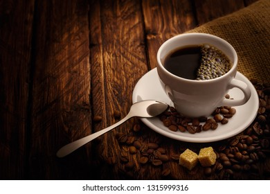 cup of coffee with a spoon of grains and cubes of sugar refined on a wooden background