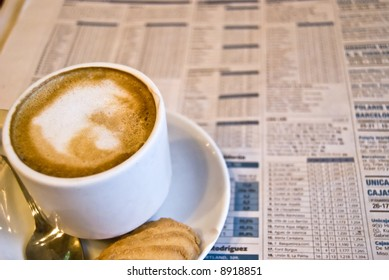 Cup of coffee, spoon and newspapers