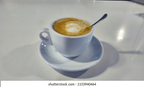 Cup of coffee with spoon on white table