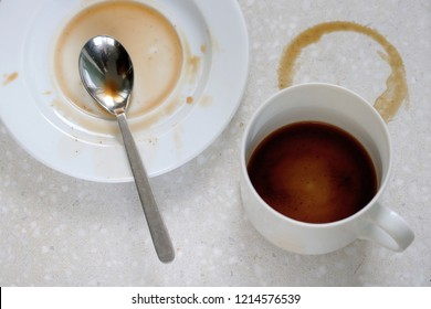 cup of coffee, spoon an spilled coffee on table and saucer