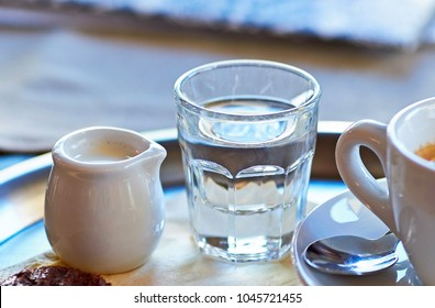 A cup of coffee with a sprig of water and milk on a tray with a biscuit
