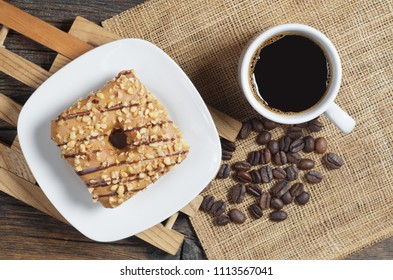 Cup of coffee and square donut with a caramel glaze is decorated with roasted nuts and chocolate stripes on rustic woode table, top view