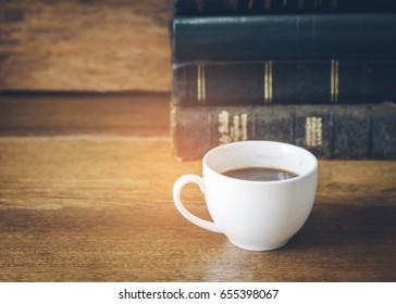a cup of coffee with stack of bible or old books on wooden background