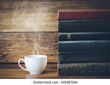 a cup of coffee and  stack of book with  holy bible on wooden background
