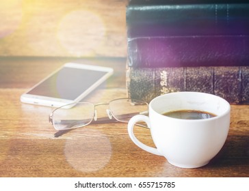 a cup of coffee with stack of old book and bible eyes glasses smartphone on wooden table