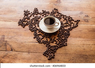 A cup of coffee standing on coffee beans laid out in the shape of Brazil, on a wooden table