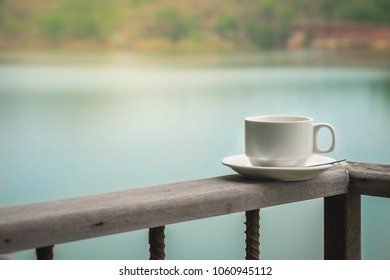 Cup of coffee standing on wooden balcony with lake background