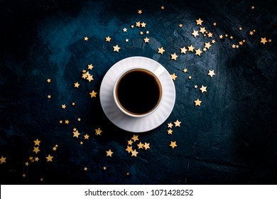 Cup of coffee and stars on a dark blue background. Concept of the Starry sky and Coffee. Flat lay, top view.