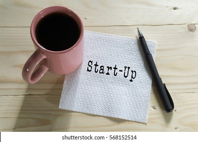 A cup of coffee with Start-Up words written on tissue paper