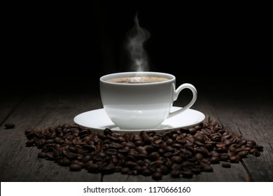 Cup of coffee with steam and coffee beans on wooden background