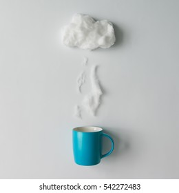 Cup of coffee with steam and cloud made of cotton wool . Flat lay. Weather concept
