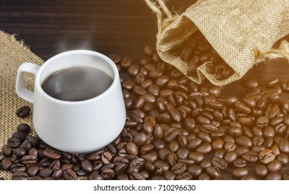 Cup of coffee and steam on table with coffee beans background.