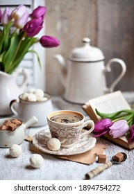 Cup of coffee with sugar cubs and coffee pot. Coffee cup, spring tulip flowers.