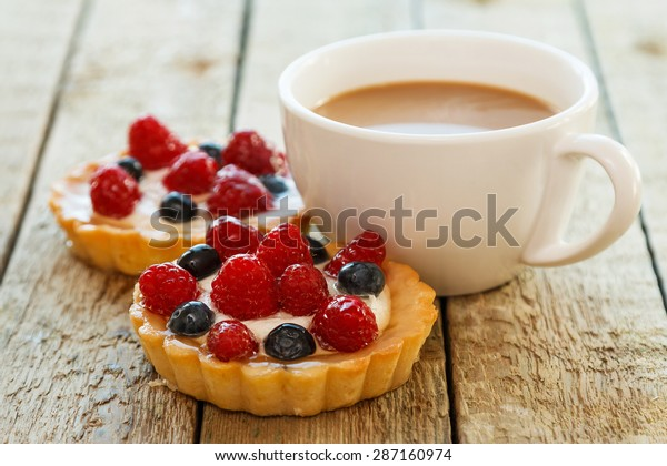 Cup of coffee and sweet cakes with berries on wooden table