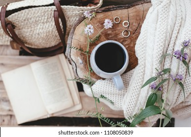 Cup coffee or tea, blanket and book outdoors on rustic stump. Relaxing and reading in the garden. Summer hygge scene, top view.