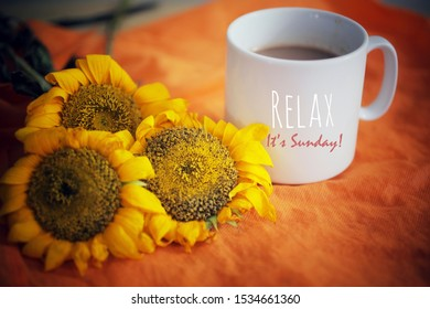 Cup of coffee or tea and flowers arrangement on orange background. With self reminder text on white mug - Relax. It is Sunday.