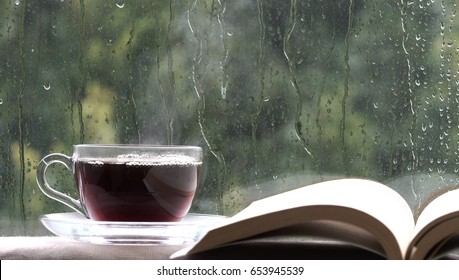 Cup of coffee tea hot drink on window sill and book