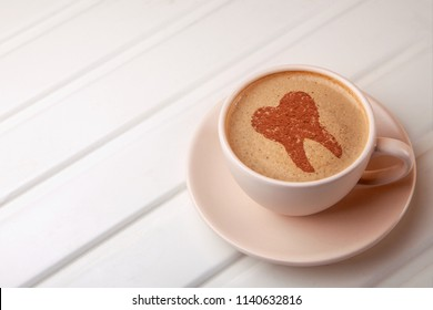 Cup of coffee with tooth on foam. Coffee spoils teeth and makes them yellow. Morning coffee or coffee break