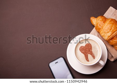 Cup of coffee with a tooth on the foam. Coffee spoils teeth and makes them yellow. Morning coffee or a coffee break with a croissant. Smartphone on the table