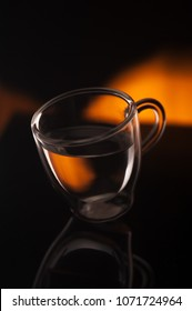 A cup of coffee in transparent glass shot in studio with reflection on dark background