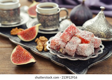 Cup of coffee with turkish delight  and metal oriental tray on wooden background