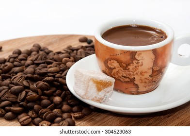 A cup of coffee and Turkish delight on a wooden board and raw coffee beans.