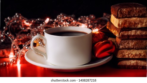 Cup of coffee and turron. Selective focus. Blurred background. Traditional Spanish Christmas candy. Christmas lights and tree decorations in the background. Low key lighting.