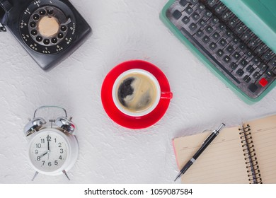 A cup of coffee with typewriter , alarm clock , telephone , notebook . top view image
