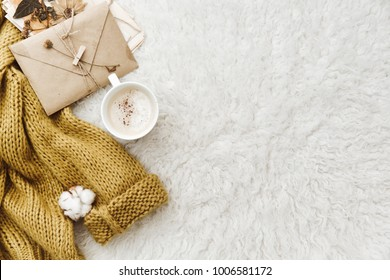 Cup of coffee, warm sweater and envelope. Flat lay composition. lazy morning, warm winter mood, blogger concept